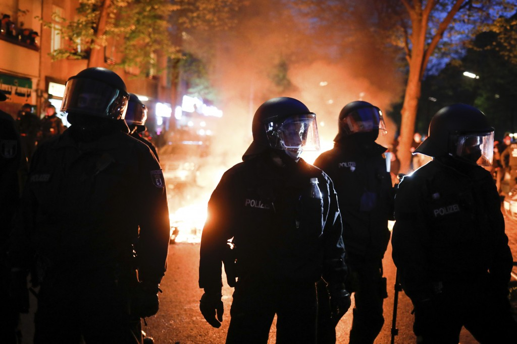 Police officers stand in front of a fire set up by demonstrators during a May Day rally in Berlin, Germany, Saturday, May 1, 2021. (AP Photo/Markus Sc...
