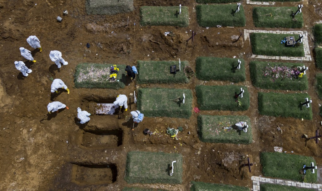 In an aerial view, workers bury a coffin containing the body of a COVID-19 victim at a cemetery reserved for those who died of complications related t...