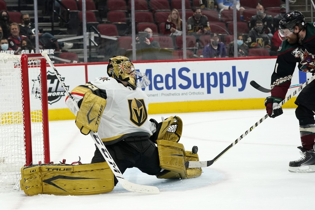 Vegas Golden Knights goaltender Marc-Andre Fleury, left, makes a save on a shot from Arizona Coyotes right wing Phil Kessel, right, during the first p...