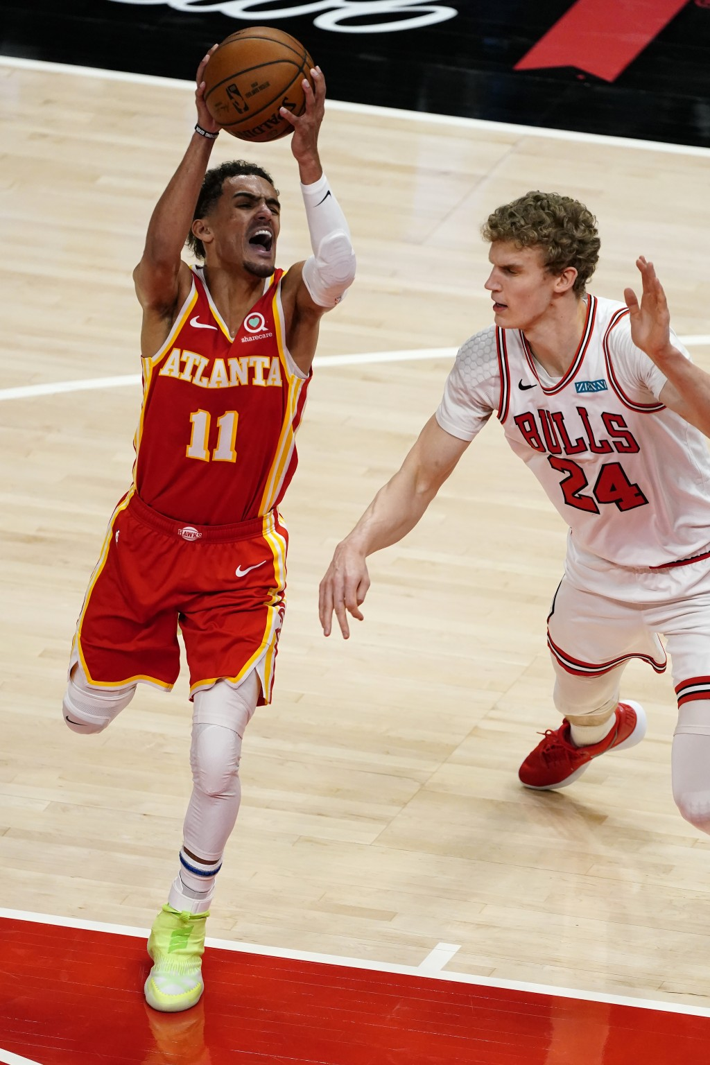 Atlanta Hawks guard Trae Young (11) goes in for a basket as Chicago Bulls forward Tomas Satoransky (24) defends in the first half of an NBA basketball...