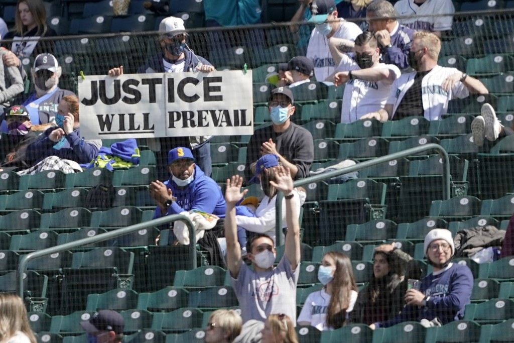 A fan holds a sign supporting Seattle Mariners starting pitcher Justus Sheffield during the fifth inning of a baseball game between the Mariners and t...