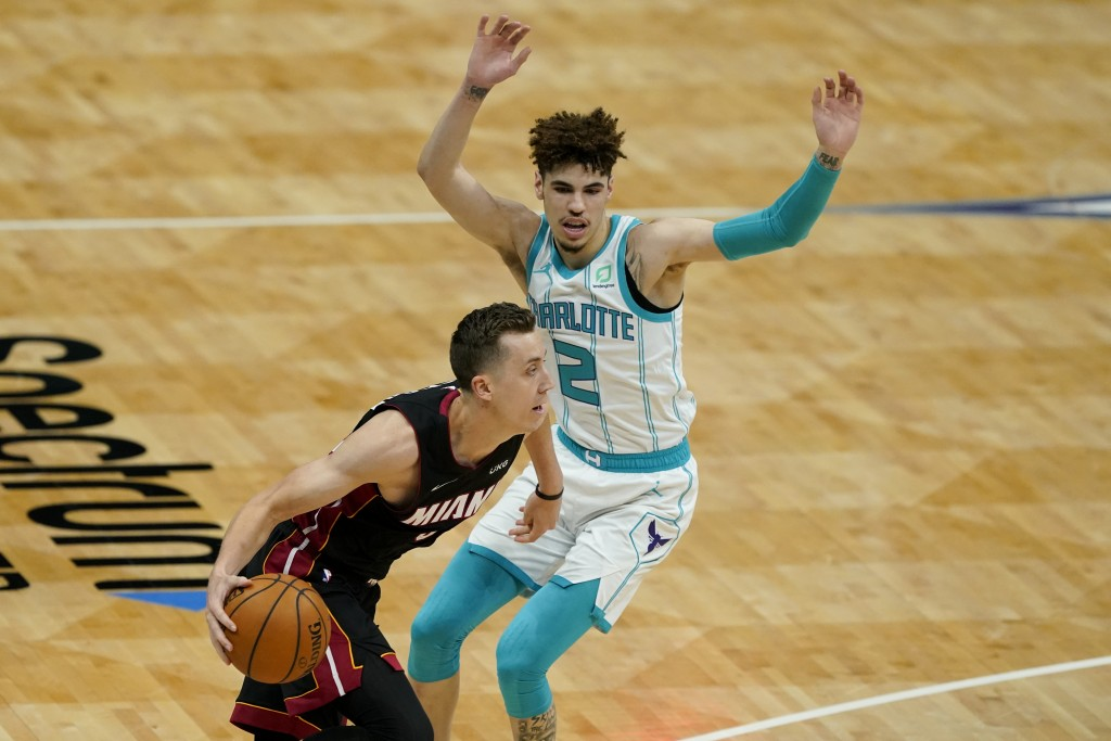 Miami Heat guard Goran Dragic drives to the basket past Charlotte Hornets guard LaMelo Ball during the first half of an NBA basketball game on Sunday,...