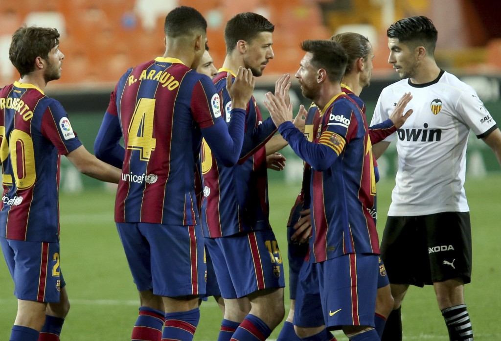 Barcelona's Lionel Messi celebrates with team mates the victory of his team at the end of a Spanish La Liga soccer match against Valencia at the Mesta...