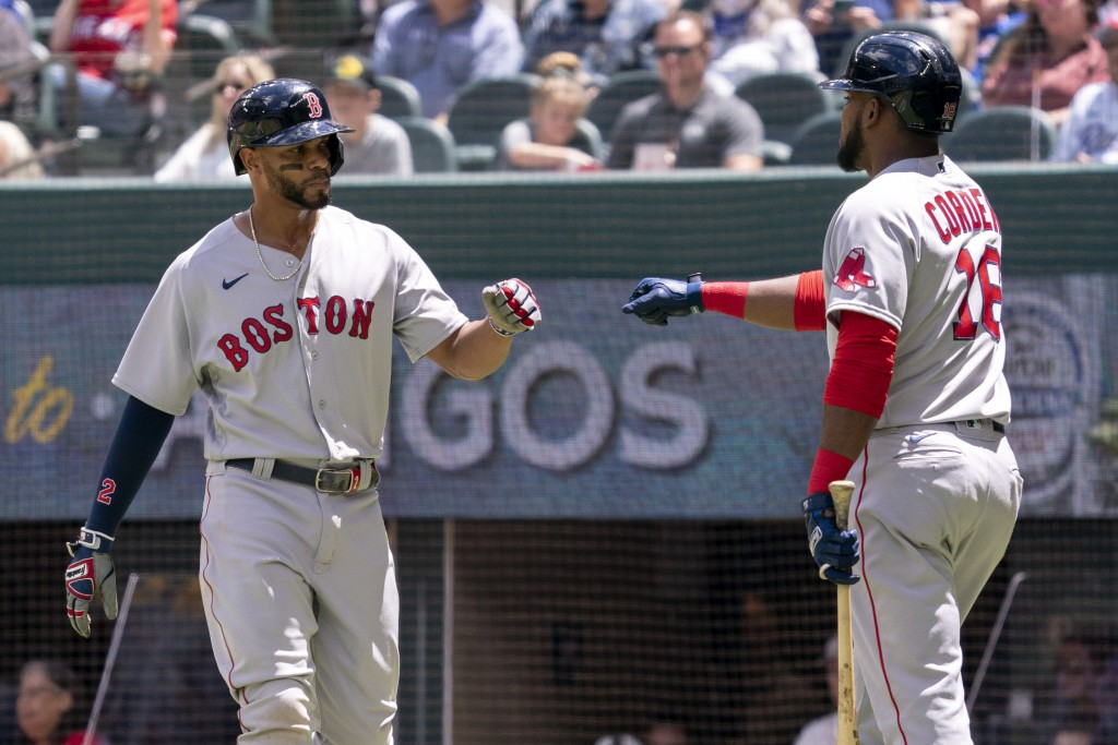 Boston Red Sox's Xander Bogaerts, left, is congratulated by Franchy Cordero (16) after scoring on a groundout by Hunter Renfroe during the first innin...