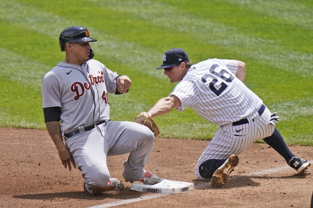 Detroit Tigers' Wilson Ramos, left, slides safely into third past New York Yankees third baseman DJ LeMahieu during the third inning of a baseball gam...