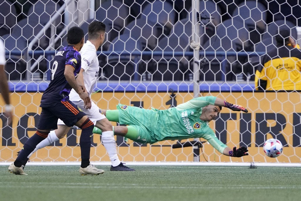 Los Angeles Galaxy goalkeeper Jonathan Bond dives but can't stop a goal kicked by Seattle Sounders forward Raul Ruidiaz, left, during the first half o...