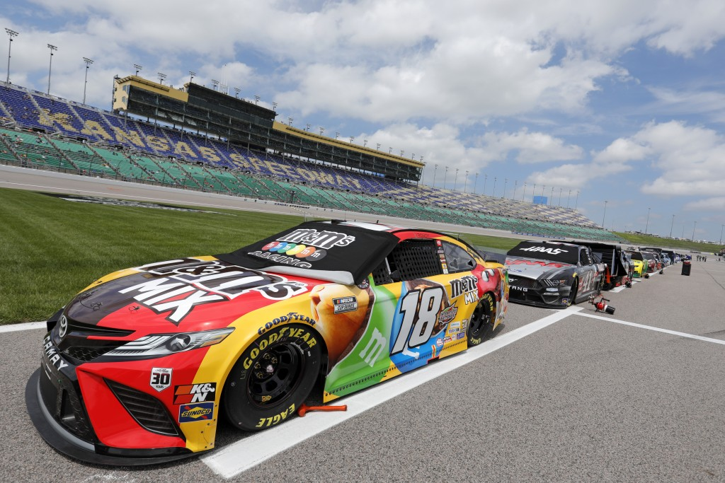 Kyle Busch's 18 car and others are parked along pit road before the start of a NASCAR Cup Series auto race at Kansas Speedway in Kansas City, Kan., Su...