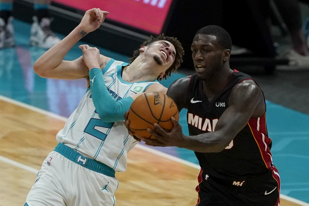 Miami Heat guard Kendrick Nunn, right, pulls a pass away from Charlotte Hornets guard LaMelo Ball during the first half of an NBA basketball game on S...