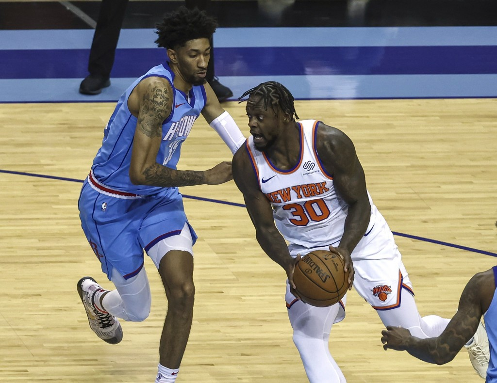 New York Knicks forward Julius Randle (30) drives with the ball as Houston Rockets center Christian Wood (35) defends during the first quarter of an N...