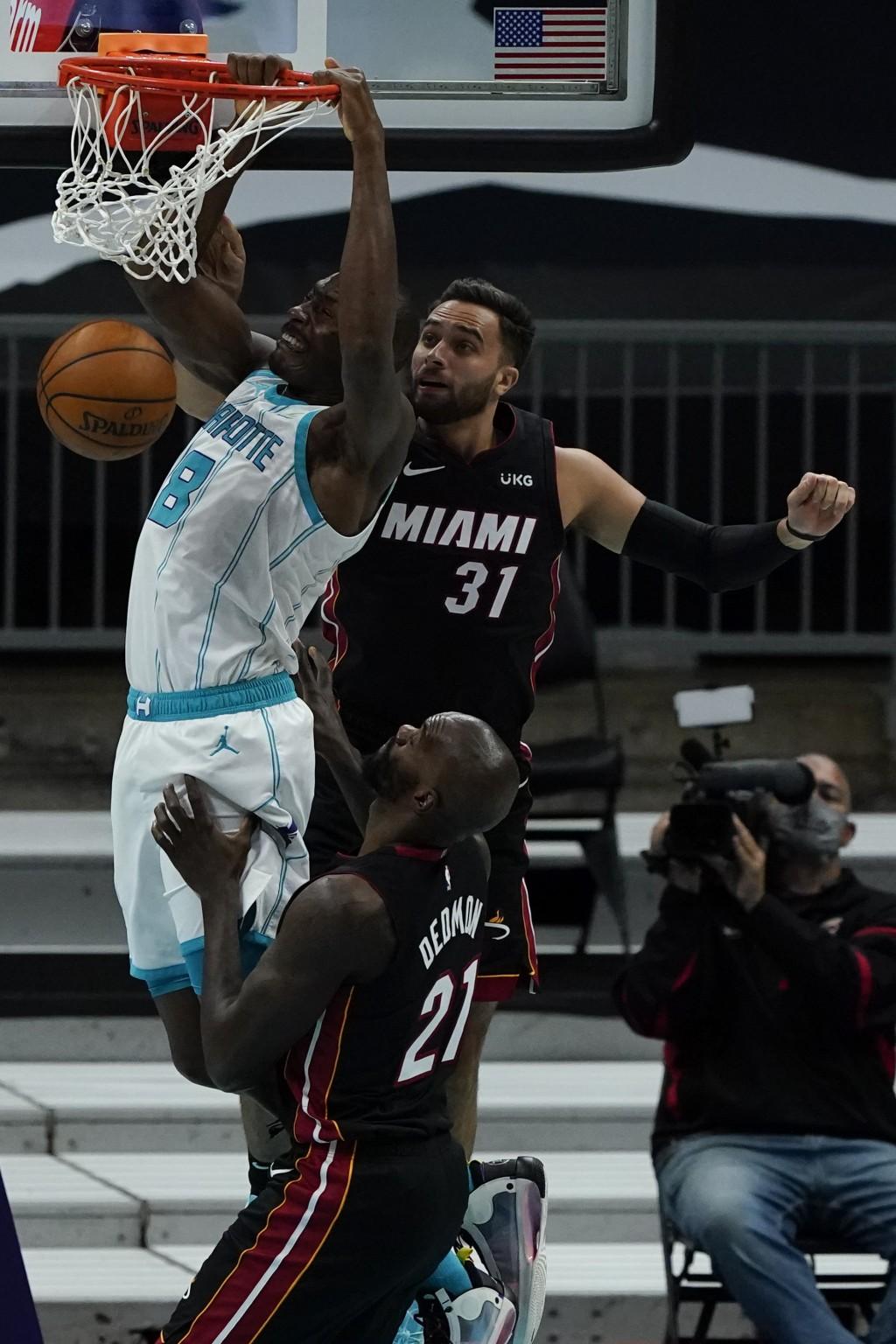 Charlotte Hornets center Bismack Biyombo dunks past Miami Heat guard Max Strus (31) and center Dewayne Dedmon during the first half of an NBA basketba...