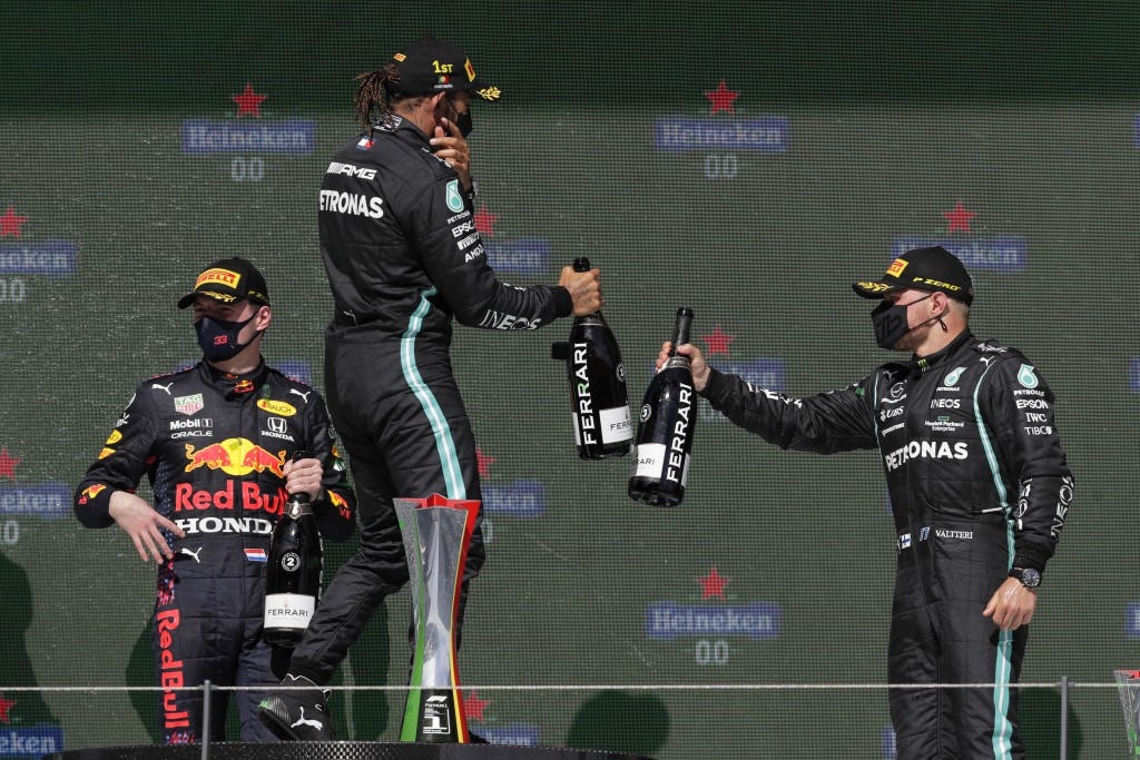 Winner Mercedes driver Lewis Hamilton of Britain celebrates with third placed Mercedes driver Valtteri Bottas of Finland, right, while second placed R...