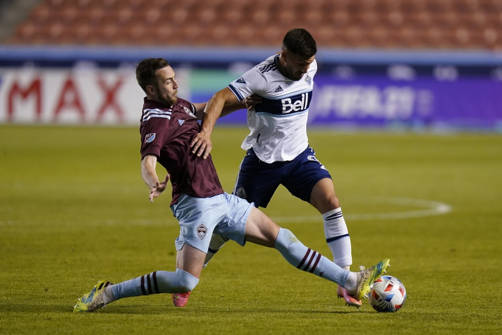 Colorado Rapids defender Danny Wilson, left, and Vancouver Whitecaps forward Lucas Cavallini battle for the ball in the second half of an MLS soccer g...