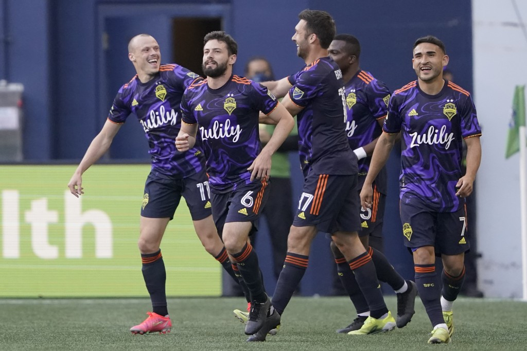 Seattle Sounders defender Brad Smith, left, celebrates with teammates including Joao Paulo (6), Will Bruin (17) and Cristian Roldan (7) after Smith sc...
