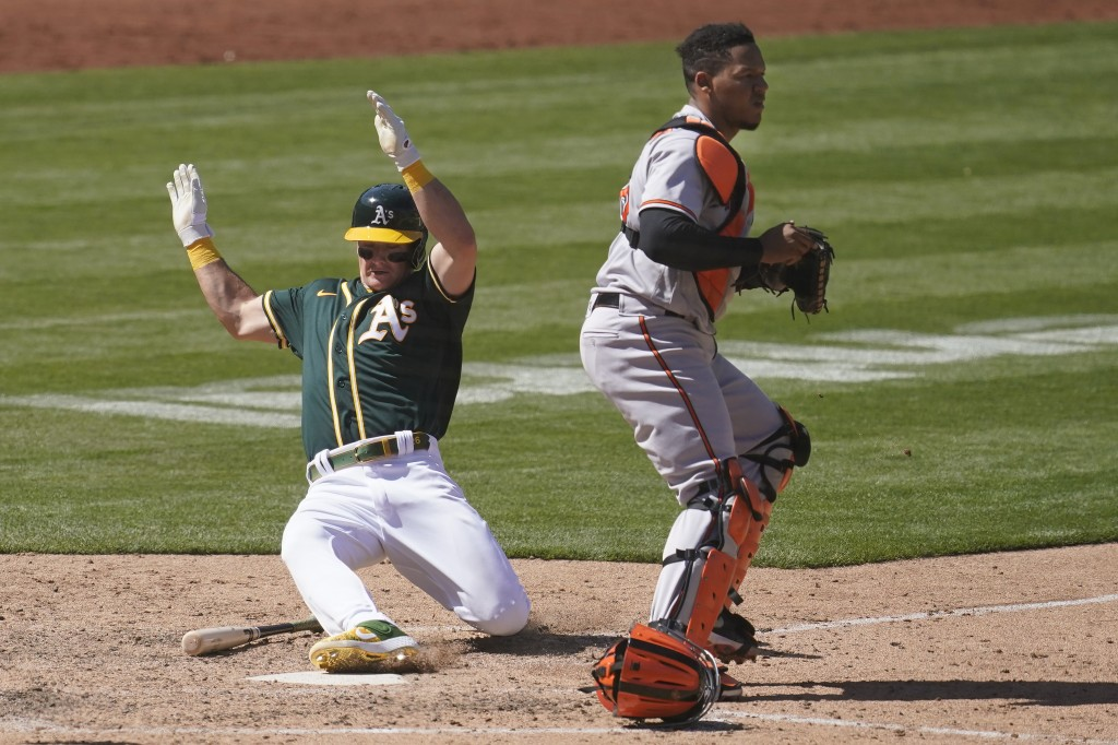 Oakland Athletics' Matt Chapman, left, scores next to Baltimore Orioles catcher Pedro Severino during the seventh inning of a baseball game in Oakland...