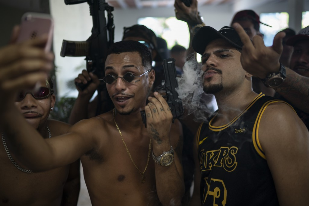 """EDS NOTE: OBSCENITY - Trap artist Marcos Borges, known as """"MbNaVoz,"""" holds an Airsoft gun during a livestream as he records a music video for the song..."""