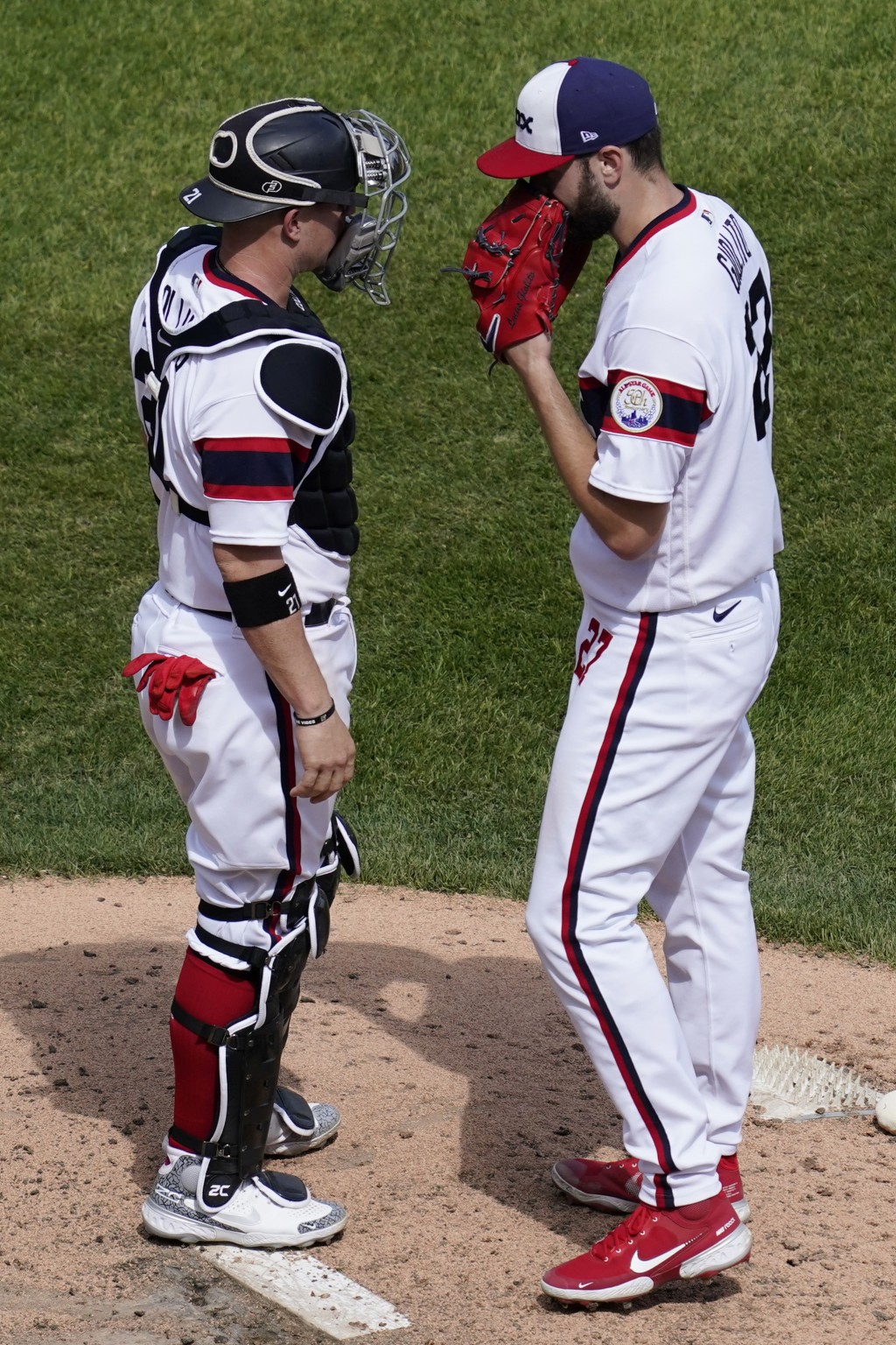 Chicago White Sox starting pitcher Lucas Giolito, right, talks with Chicago White Sox catcher Zack Collins during the fifth inning of a baseball game ...