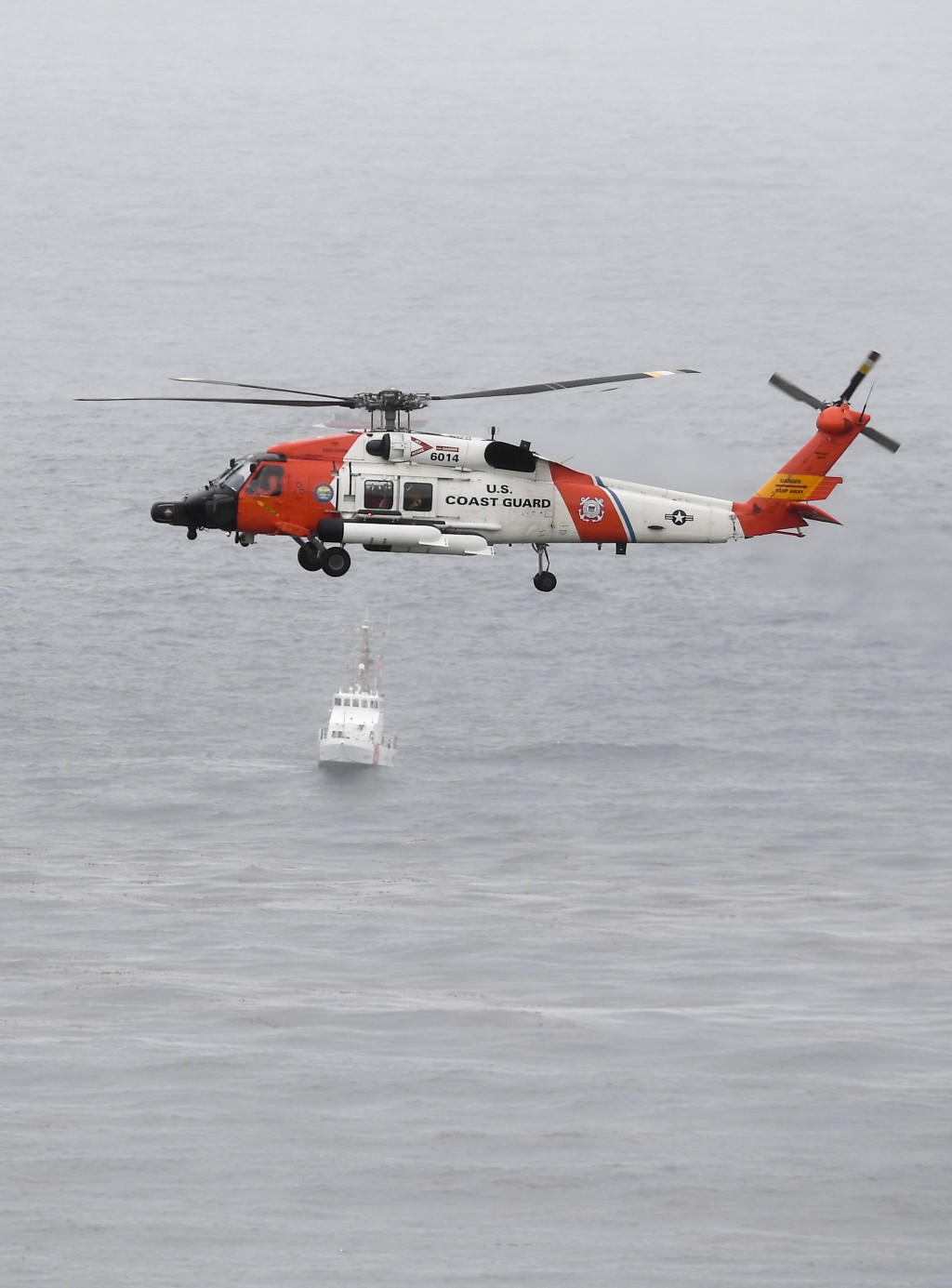 A U.S. Coast Guard helicopter flies over boats searching the area where a boat capsized just off the San Diego coast Sunday, May 2, 2021, in San Diego...