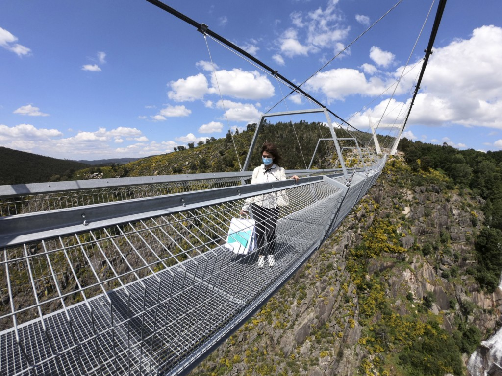 A woman walks across a narrow footbridge suspended across a river canyon, which claims to be the world's longest pedestrian bridge, in Arouca, norther...