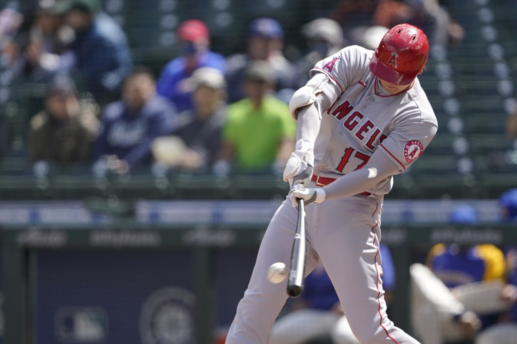Los Angeles Angels Shohei Ohtani hits into a play where he reached first base on a fielding error during the third inning of a baseball game, Sunday, ...