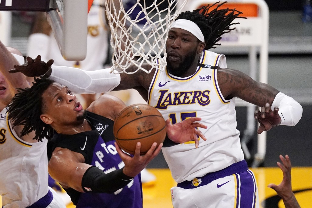 Toronto Raptors forward Freddie Gillespie, left, shoots as Los Angeles Lakers center Montrezl Harrell defends during the second half of an NBA basketb...