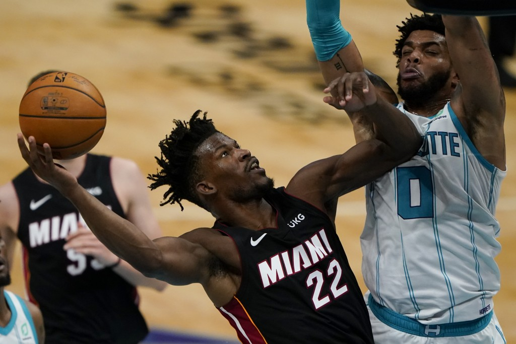 Miami Heat forward Jimmy Butler shoots over Charlotte Hornets forward Miles Bridges during the first half of an NBA basketball game on Sunday, May 2, ...