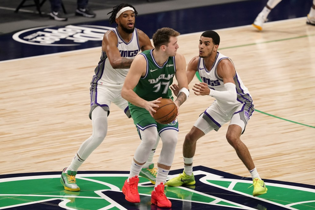 Sacramento Kings' Marvin Bagley III, left rear, and Justin James, right, defend as Dallas Mavericks guard Luka Doncic (77) advances the ball in the se...