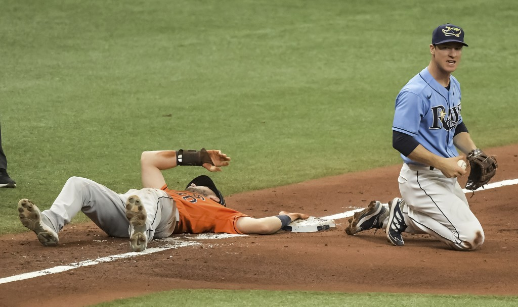 Tampa Bay Rays' Joey Wendle, right, holds the ball after Houston Astros' Kyle Tucker, left, beat the tag at third base on a throw from Rays center fie...