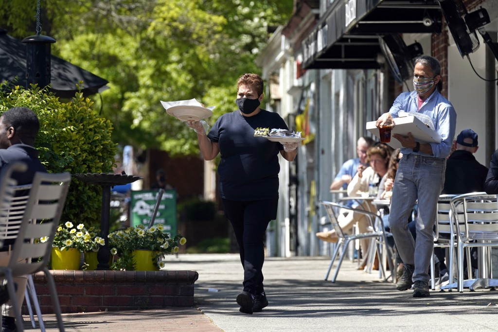 A member of the wait staff takes food to outdoor diners at the Mediterranean Deli restaurant in Chapel Hill, N.C., Friday, April 16, 2021. Thousands o...