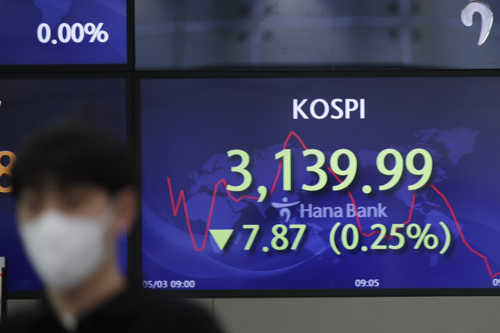 A currency trader walks by a screen showing the Korea Composite Stock Price Index (KOSPI) at a bank's foreign exchange dealing room in Seoul, South Ko...
