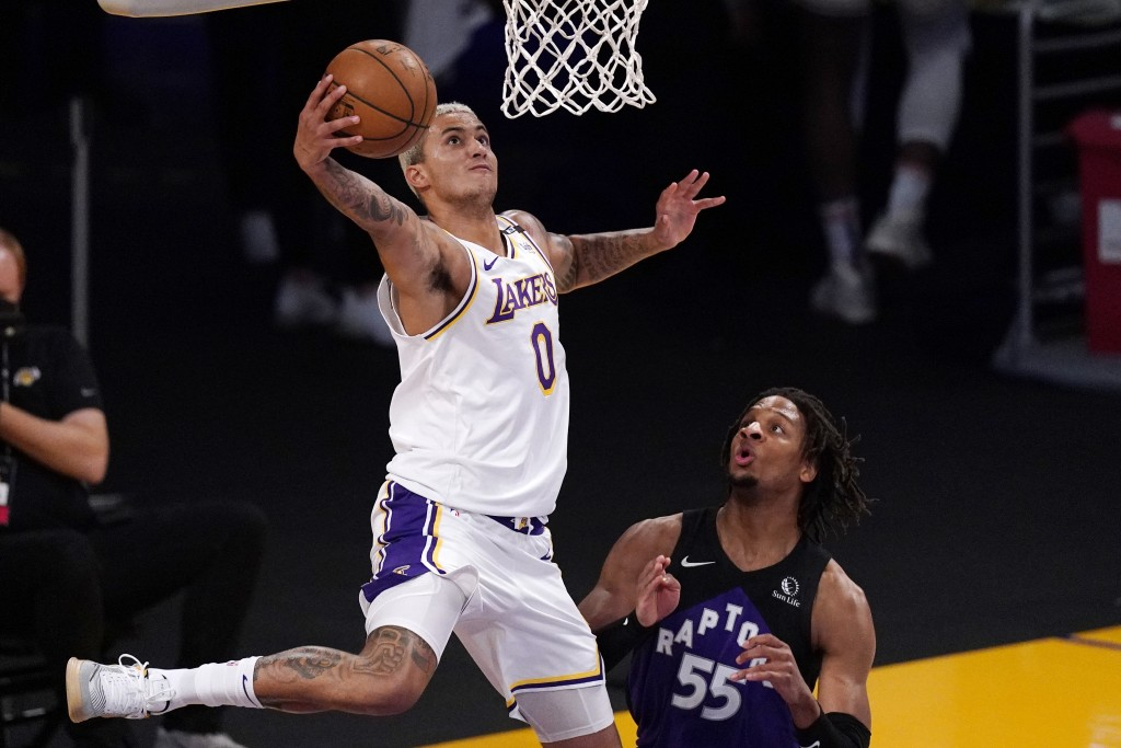 Los Angeles Lakers forward Kyle Kuzma, left, shoots as Toronto Raptors forward Freddie Gillespie defends during the first half of an NBA basketball ga...