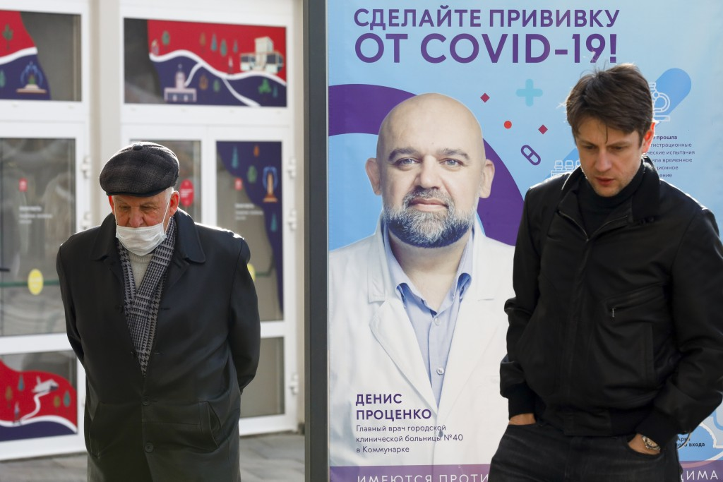 Two men, one of them wearing a face mask, stand near a vaccination point decorated with the poster showing a portrait of Dr. Denis Protsenko and words...