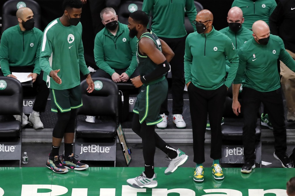 Boston Celtics' Jaylen Brown, center, limps off the court after colliding with teammate Jayson Tatum during the second half of an NBA basketball game ...