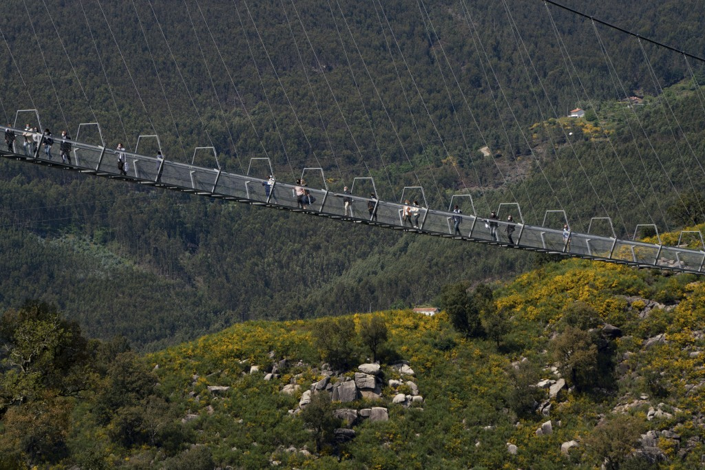 People walk across a narrow footbridge suspended across a river canyon, which claims to be the world's longest pedestrian bridge, in Arouca, northern ...
