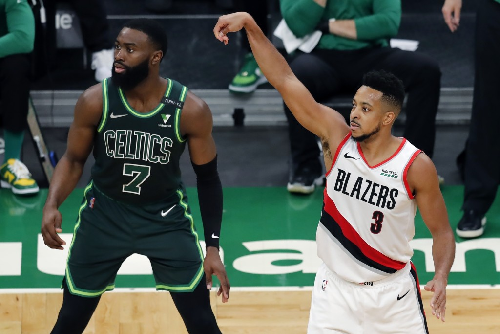 Portland Trail Blazers' CJ McCollum (3) shoots a 3-pointer against Boston Celtics' Jaylen Brown (7) during the second half of an NBA basketball game, ...