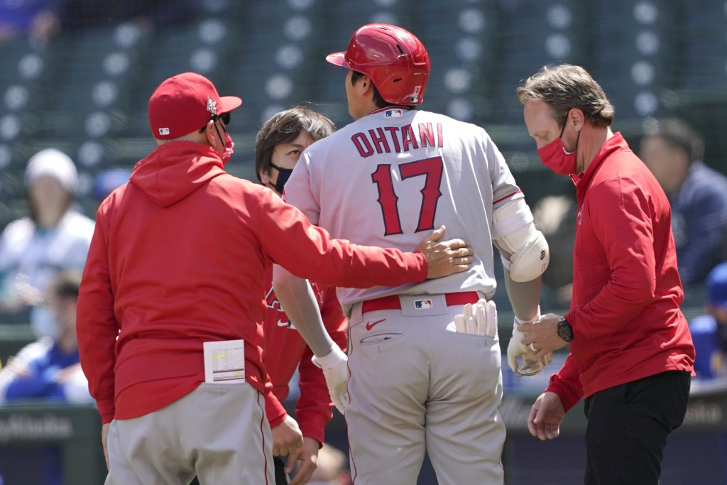 Los Angeles Angels Shohei Ohtani (17), talks with a trainer, right, and manager Joe Maddon, left, after he was hit by a pitch during the first inning ...