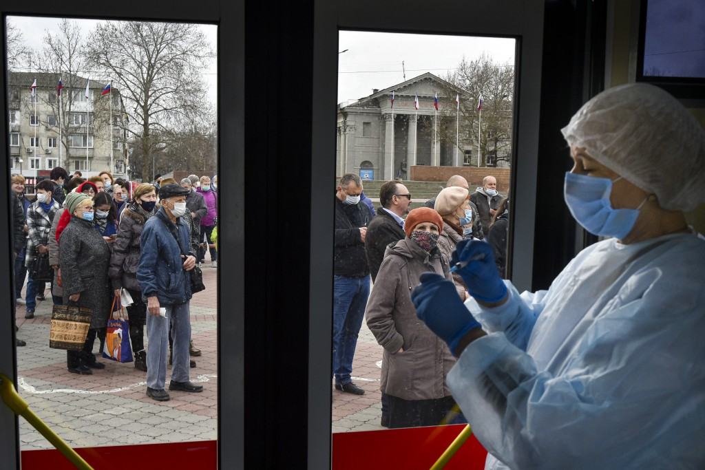 A Russian medical worker prepares a shot of Russia's Sputnik V coronavirus vaccine as people wearing face masks to protect against coronavirus queue t...
