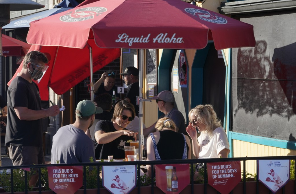 FILE - In this March 31, 2021 file photo, people drink outdoors on the patio of Big Dean's Ocean Front Cafe, decorated with beer banners with the imag...