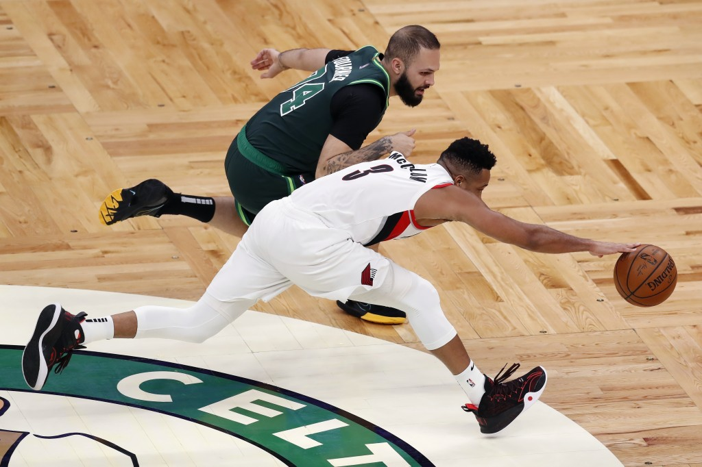 Boston Celtics' Evan Fournier (94) and Portland Trail Blazers' CJ McCollum (3) battle for a loose ball during the second half of an NBA basketball gam...