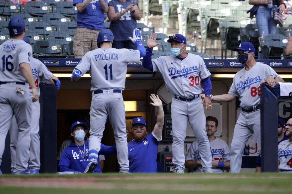 Los Angeles Dodgers' AJ Pollock (11) is congratulated by manager Dave Roberts (30) after hitting a three-run home run during the sixth inning of a bas...