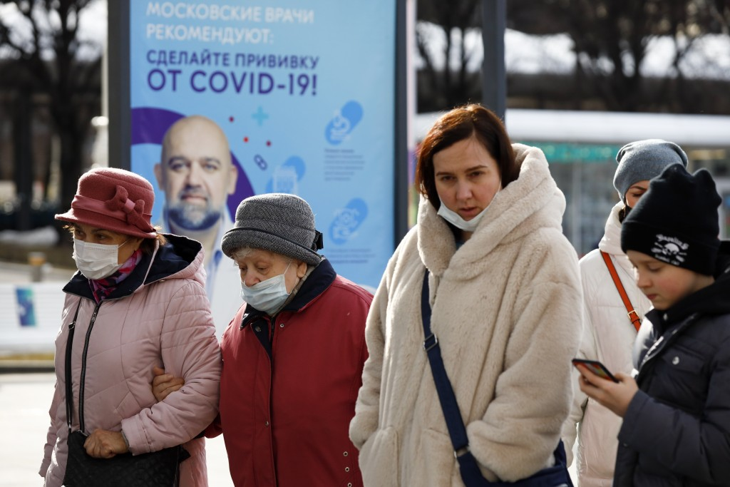 """A group of people some of them wearing face masks walk past the poster showing a portrait of Dr. Denis Protsenko and words reading """"Get vaccinated aga..."""