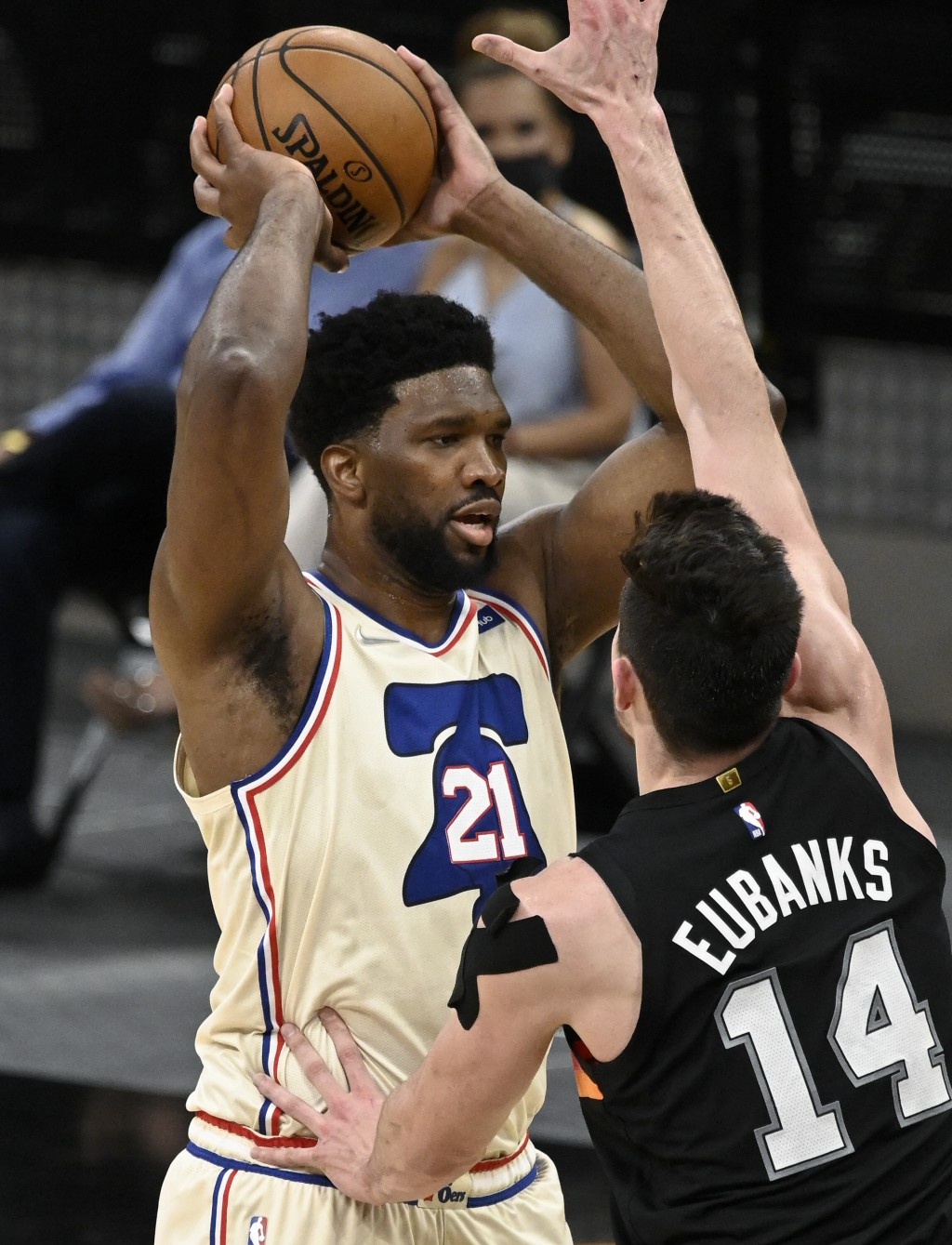 Philadelphia 76ers' Joel Embiid (21) looks to pass as he is defended by San Antonio Spurs' Drew Eubanks during the second half of an NBA basketball ga...