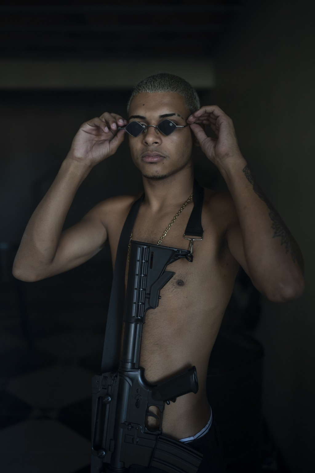 """Trap artist Filipe Toledo, known as """"Lindinho 22,""""  poses for a photo with an Airsoft gun during the recording of a 'Trap de Cria' music video in the ..."""