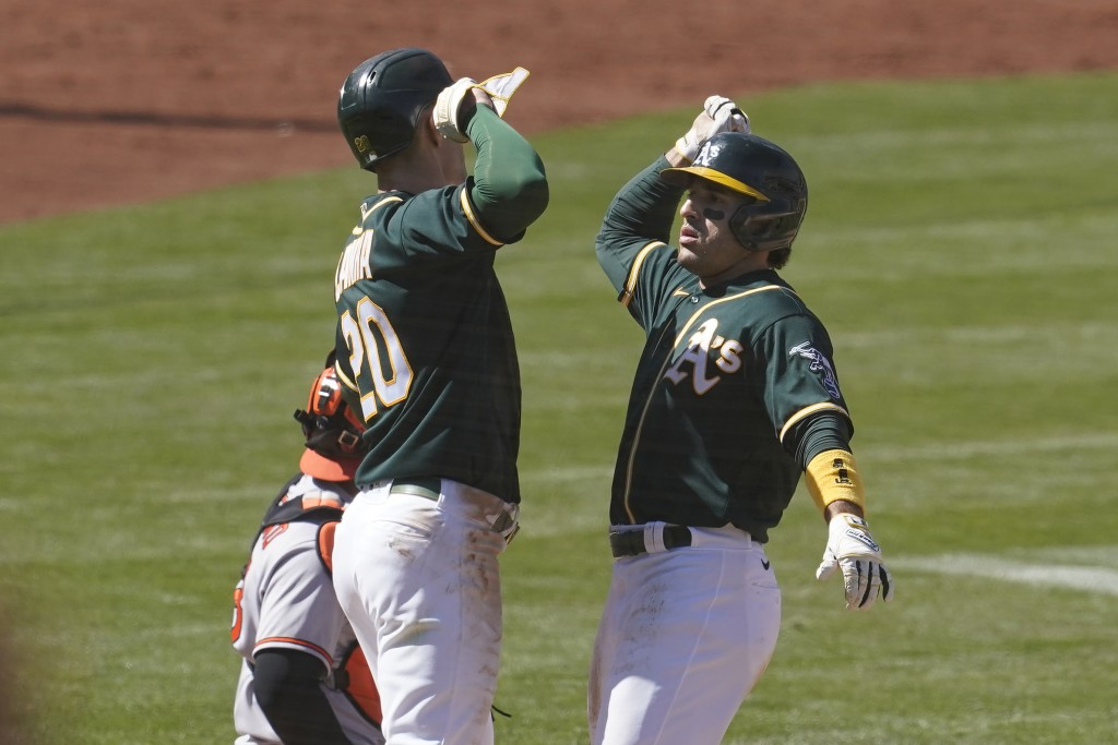 Oakland Athletics' Ramon Laureano, right, celebrates after hitting a two-run home run that scored Mark Canha, left, during the eighth inning of a base...