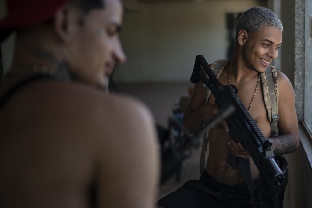 """Artist Filipe Toledo, known as """"Lindinho 22,"""" holds an Airsoft gun before the recording of a Trap de Cria music video in the Jardim Catarina community..."""