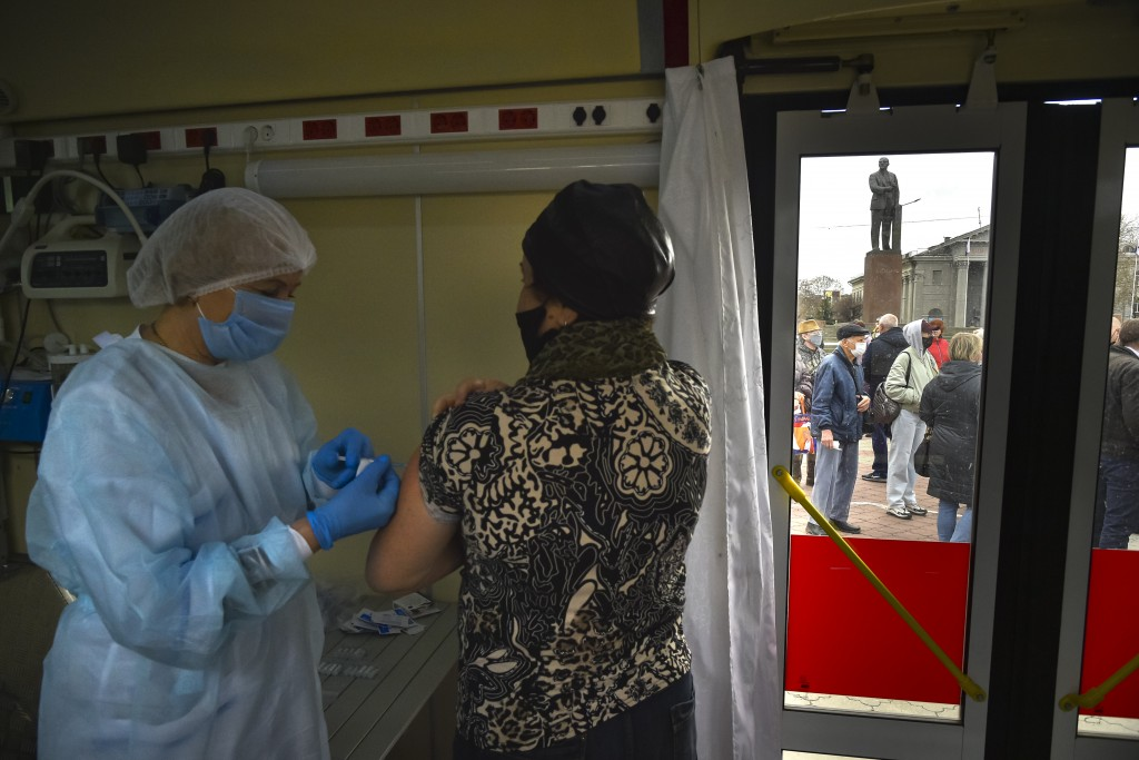 A Russian medical worker administers a shot of Russia's Sputnik V coronavirus vaccine for a woman as people wearing face masks to protect against coro...
