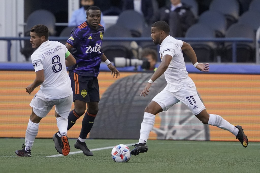 Los Angeles Galaxy forward Samuel Grandsir (11) looks to pass as Seattle Sounders defender Nouhou, center, looks on during the first half of an MLS so...