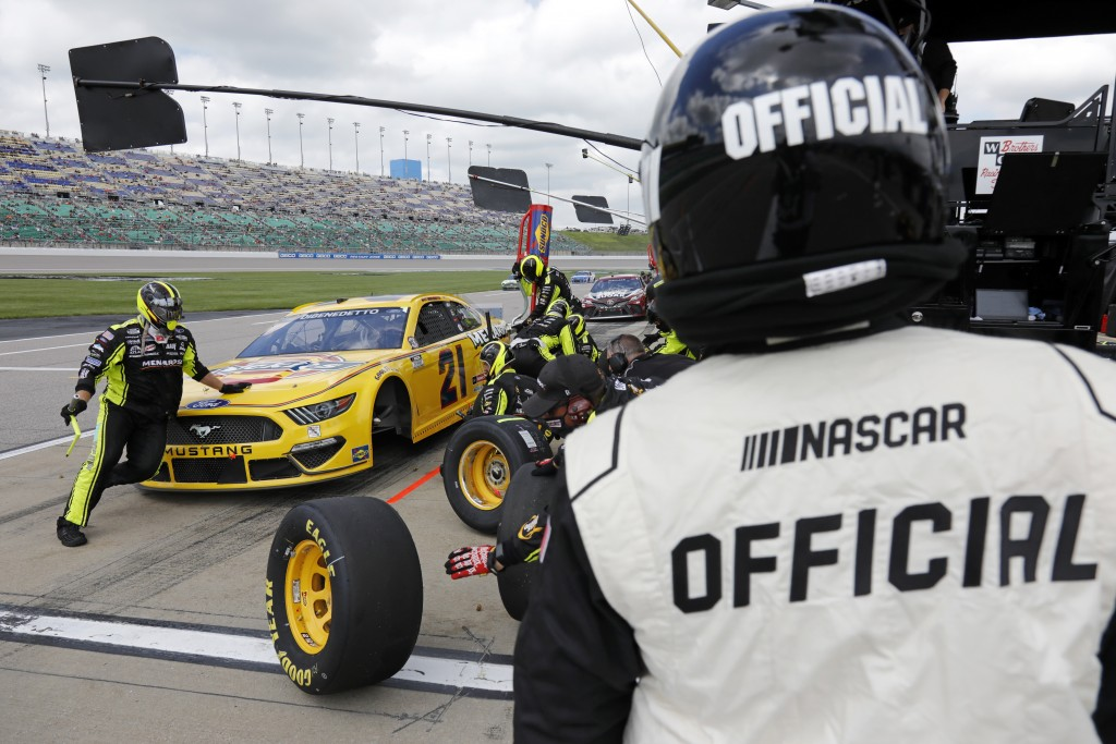 A race official looks on as Matt DiBenedetto makes a stop on pit road during a NASCAR Cup Series auto race at Kansas Speedway in Kansas City, Kan., Su...