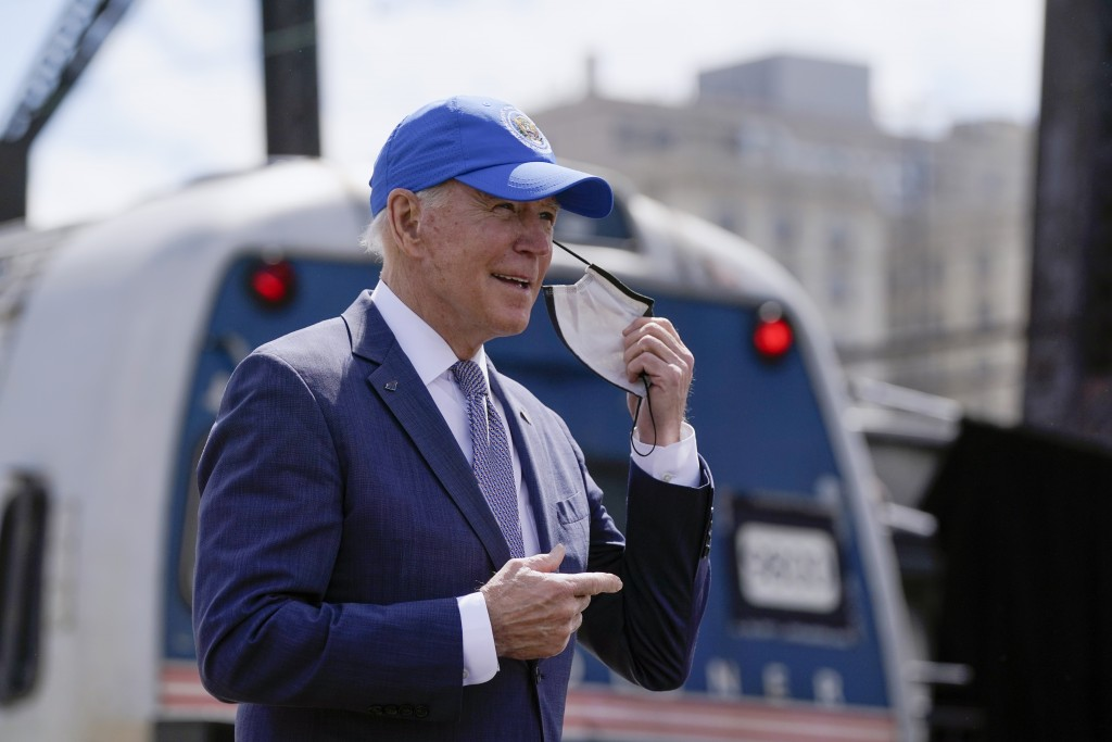 President Joe Biden removes his face mask as he arrives for an event to mark Amtrak's 50th anniversary at 30th Street Station in Philadelphia, Friday,...