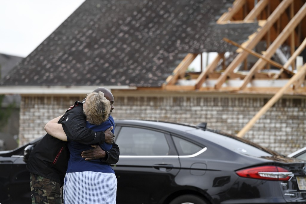 Neighbors Alfred Lee and Grace Bazzy hug in front of another neighbor's damaged home along Elvis Presley Drive in Tupelo, Miss., Monday, May 3, 2021. ...