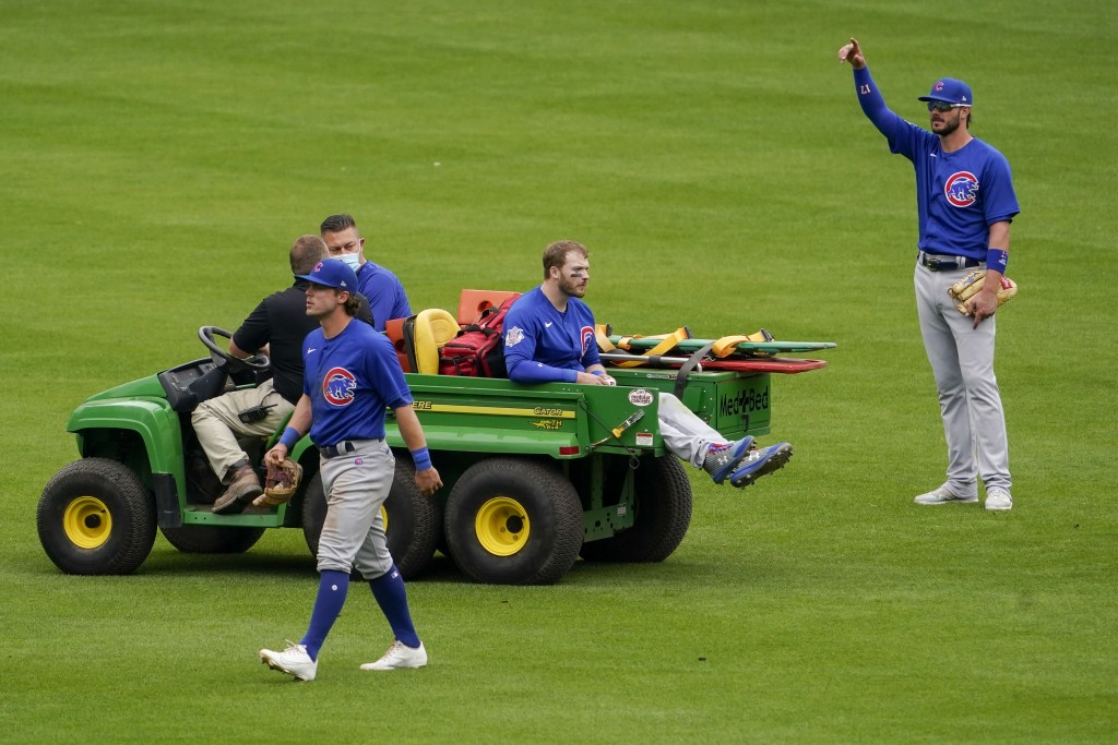 Chicago Cubs center fielder Ian Happ, center, is carted off after a collision with teammate Nico Hoerner, foreground, in the eighth inning during a ba...